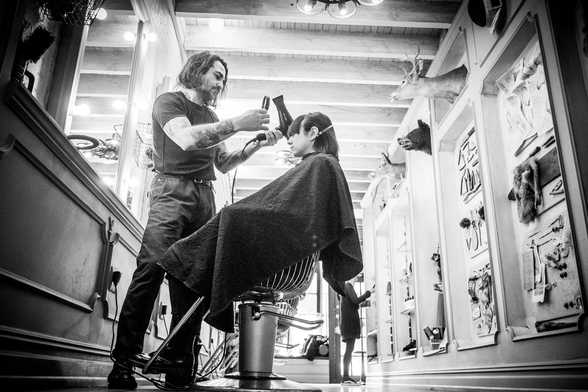 Silvestera with a client in his East Village salon, where furry heads look on.