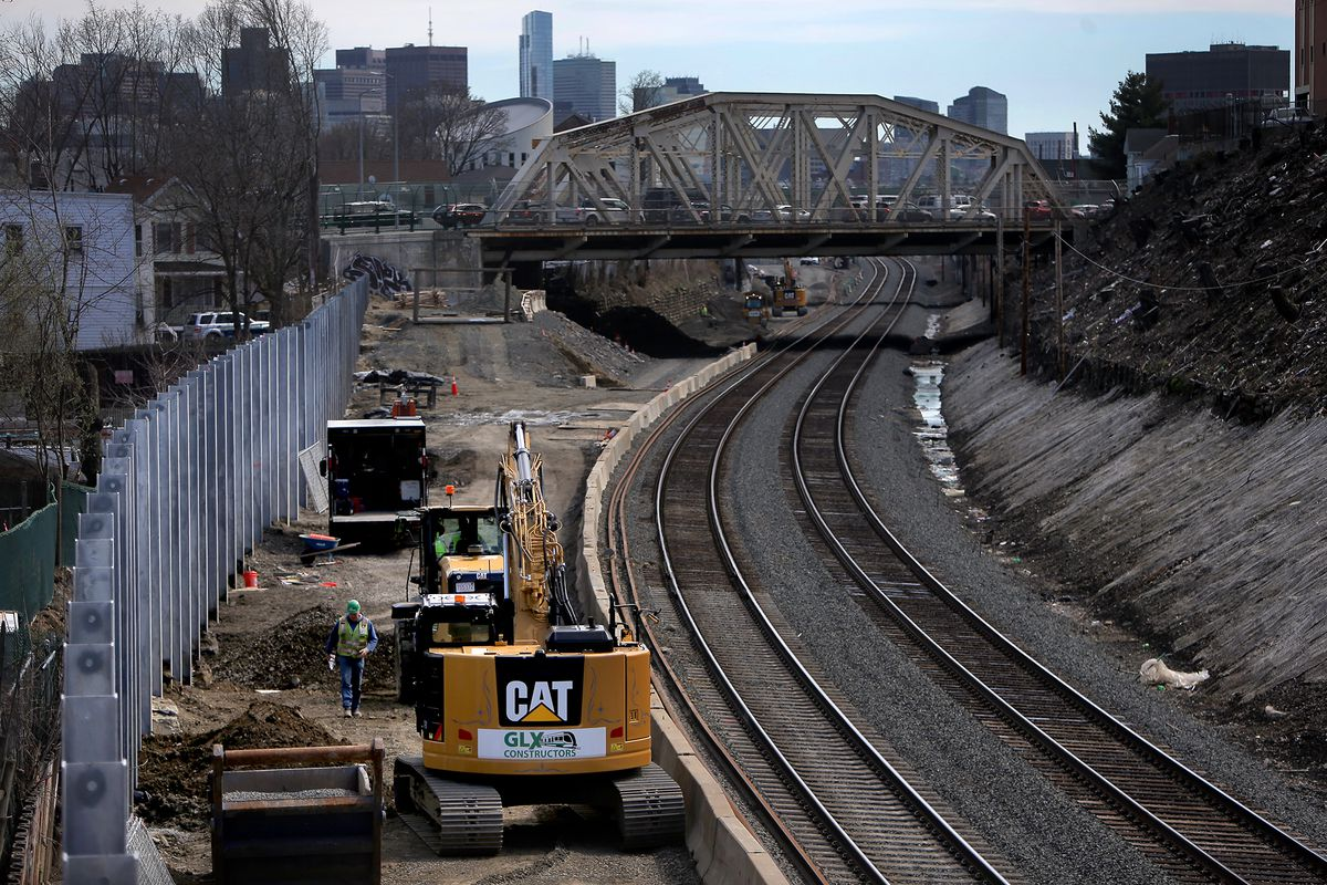 Railroad tracks heading into a city, with construction equipment to the right.