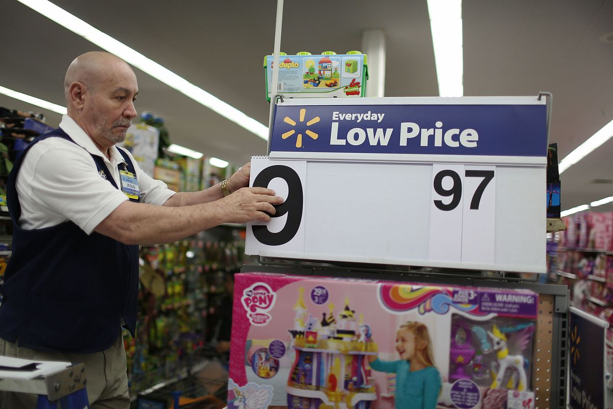 """A Walmart employee changes the """"Low Price"""" sign on a Walmart store display."""
