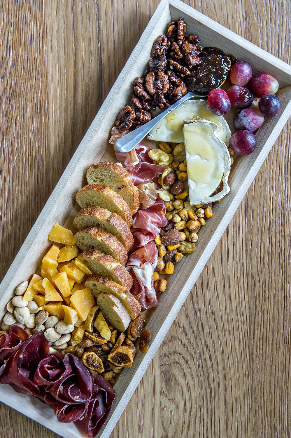 Mondo Mini's charcuterie board with a curated selection of cheese and charcuterie, bread, olives, nuts, and fruit.