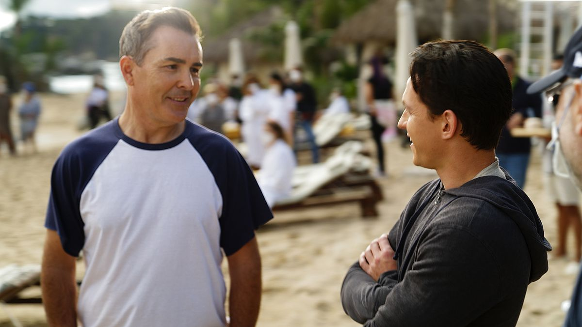 a photo of Nolan North looking at Tom Holland on the beach, on the set of the Uncharted movie