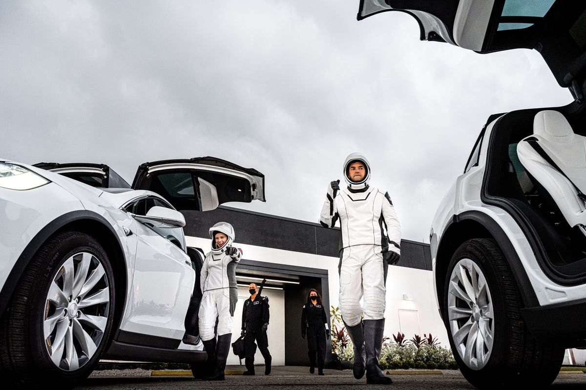 People in astronaut suits exit cars with gull-wing doors.