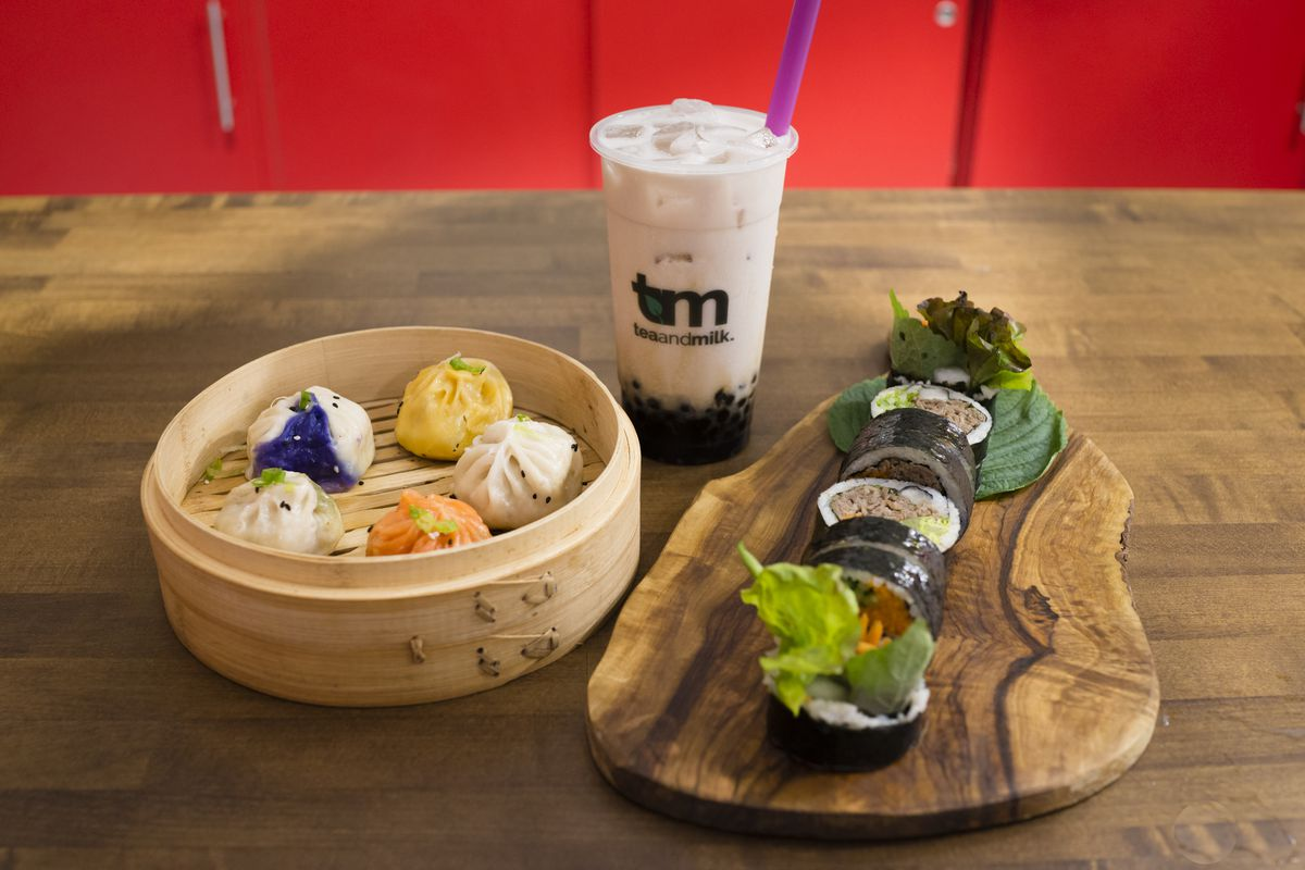 Dumplings in a bamboo steamer, a plastic cup of tea with a purple straw, and a seaweed-wrapped roll of bulgogi beef arranged on a wooden platter, all set together on a wooden table.