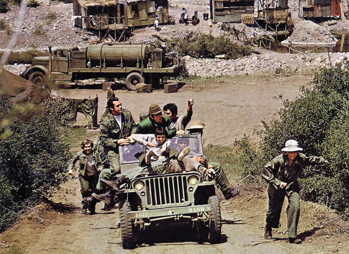 A truck packed full of soldiers attempts to make its way uphill.