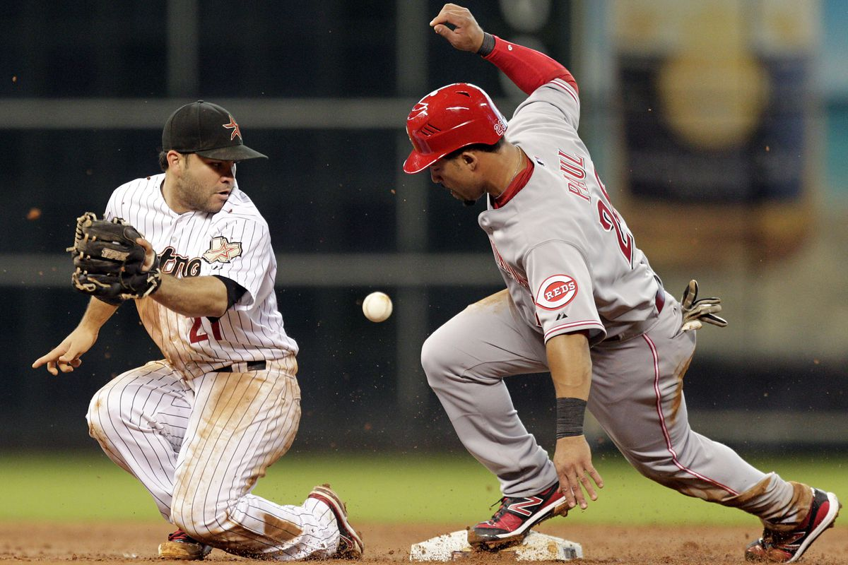HOUSTON TX - JULY 24:  Jose Altuve #27 of the Houston Astros can't handle the throw as Xavier Paul #26 of the Cincinnati Reds steals second base at Minute Maid Park on July 24, 2012 in Houston, Texas.  (Photo by Bob Levey/Getty Images)