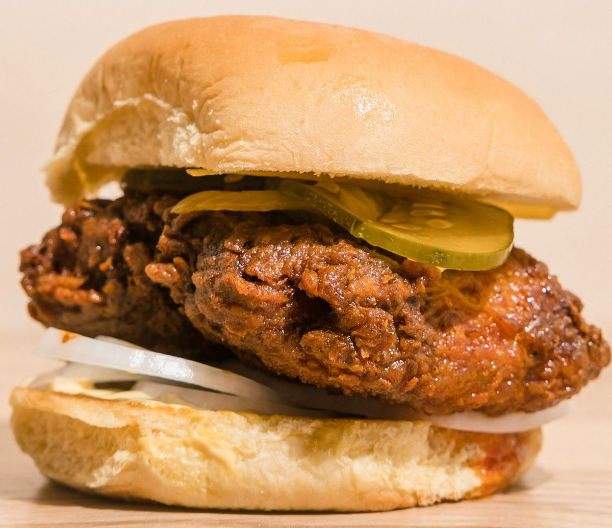 A fried fish sandwich on a bun with pickles and onions.