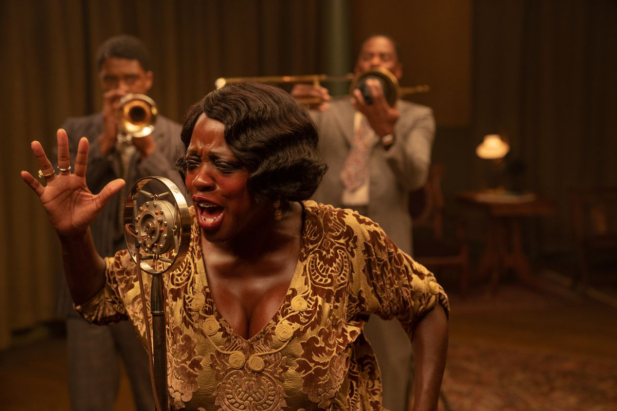 A woman sings in the foreground, while two men play trombone and trumpet in the background.
