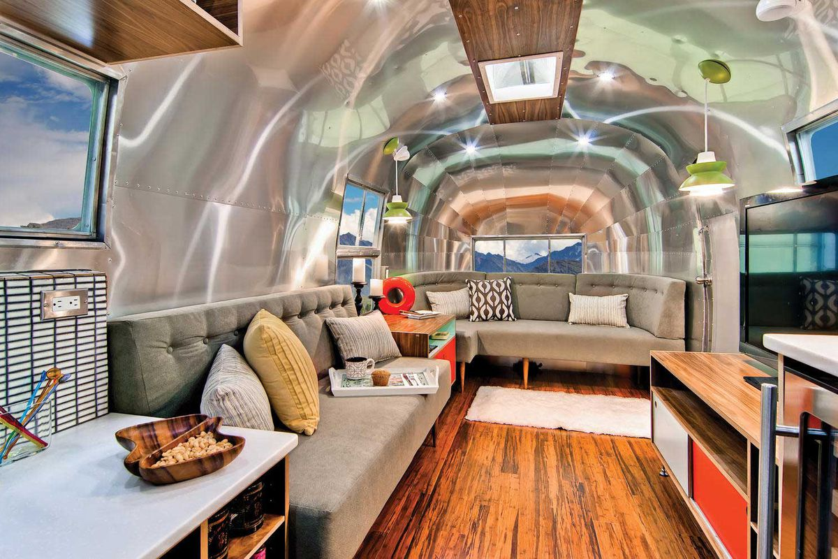 Interior of renovated airstream, with a green midcentury-inspired couch, wood floors, and gleaming aluminum interiors.