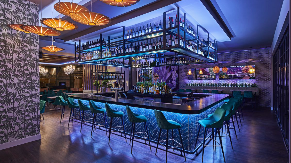 bright bar in the middle of a room surrounded by blue chairs