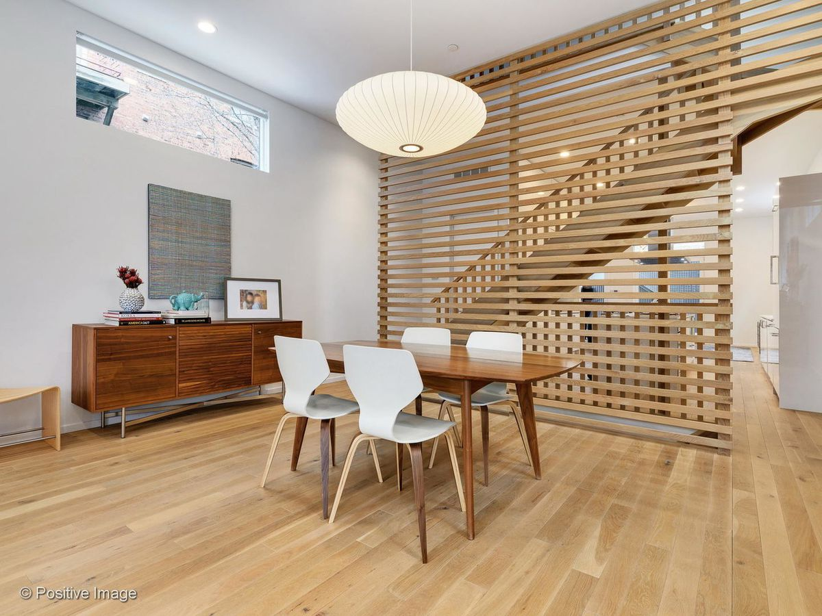 A dining room with a paper light fixture, a staircase hidden behind slatted wood, a table with four chairs, and a credenza.