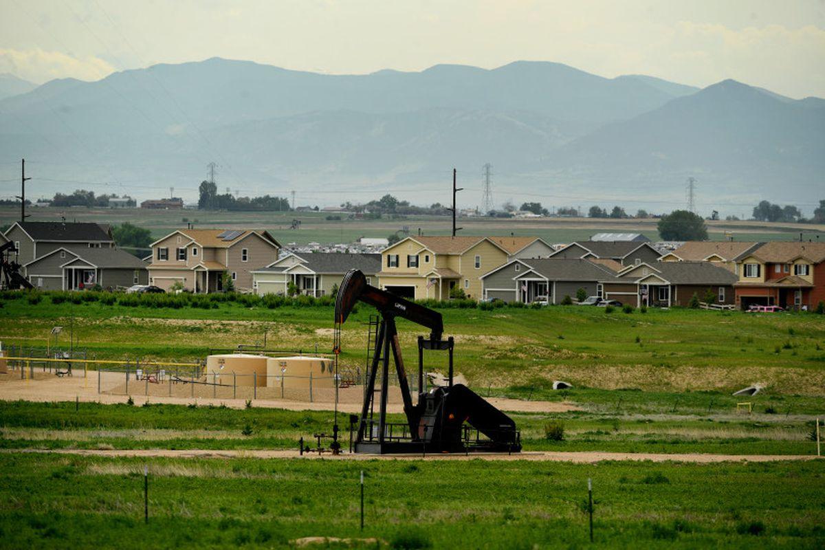 An oil derrick pumps oil near a subdivision roundabout in Dacono.