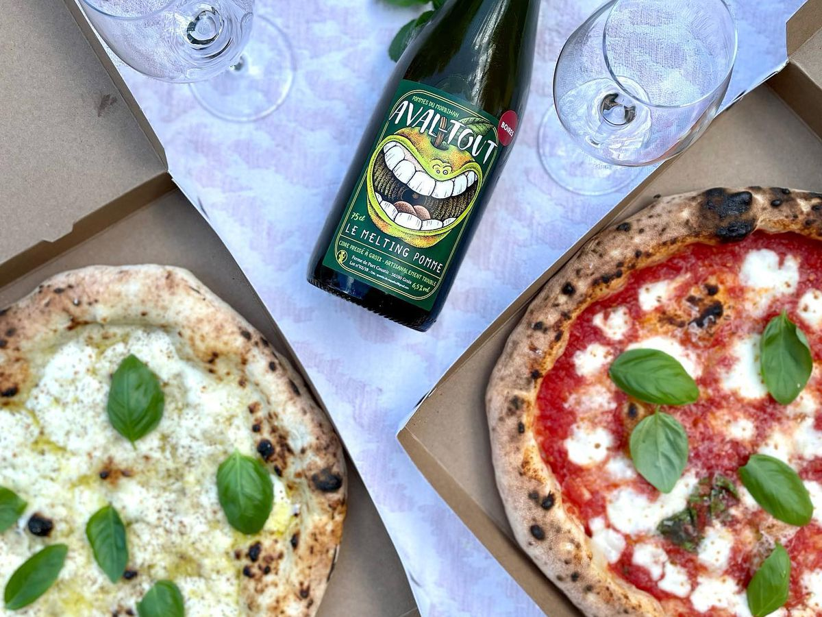 two pizzas with a bottle of wine