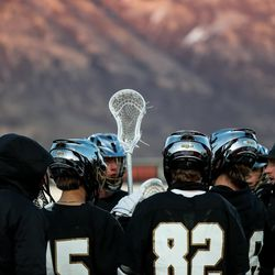 Lone Peak players huddle during a timeout in a boys lacrosse game in American Fork on Tuesday, March 30, 2021.