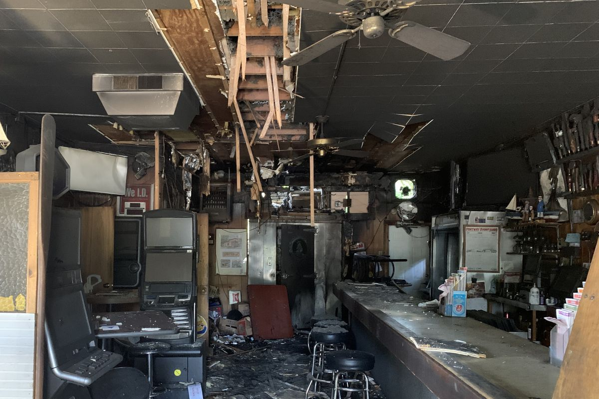 The insides of a bar after a fire, with a burnt floor and ruined ceiling.