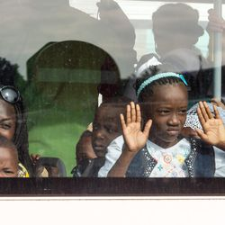 A family look out of the window of a bus after being evacuated from Brussels airport, after explosions rocked the facility in Brussels, Belgium, Tuesday March 22, 2016. Authorities locked down the Belgian capital on Tuesday after explosions rocked the Brussels airport and subway system, killing at least 34 people and injuring many more. Belgium raised its terror alert to its highest level, diverting arriving planes and trains and ordering people to stay where they were. Airports across Europe tightened security.