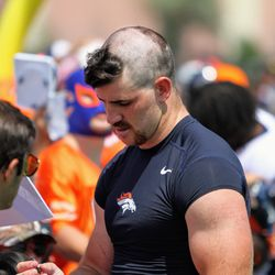 Broncos rookie ILB Josey Jewell signs autographs for fans after practice.