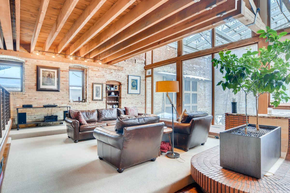 A living room has a leather couch and arm chairs, beamed ceiling, and a wall of windows.