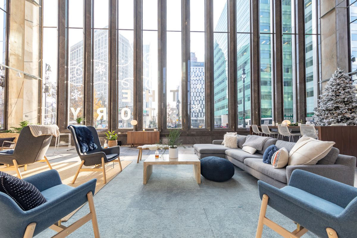 Sofas and chairs around a wooden table in front of tall windows.
