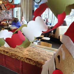 """Bayou Bakery is decked out this year with red poinsettas, and garland made by none other than chef David Guas and his sons. And since Guas is an avid motorcyclist, the pièce de résistance is a singing, motorcycle-riding Santa. The Santa sings """"Born to be"""