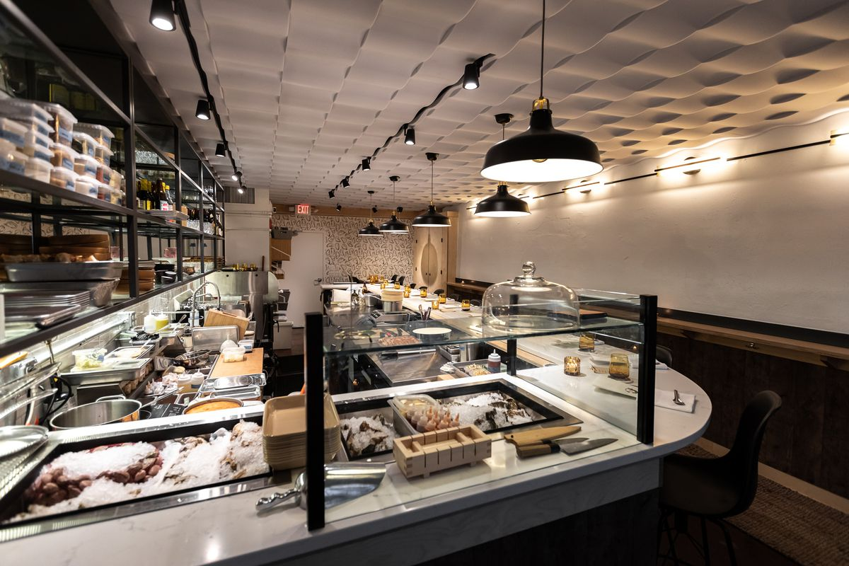 A view of the raw bar area surrounded by glass with the small galley kitchen behind the counter.
