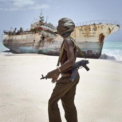 In this photo taken Sunday, Sept. 23, 2012, masked Somali pirate Abdi Ali walks past a Taiwanese fishing vessel that washed up on shore after the pirates were paid a ransom and released the crew, in the once-bustling pirate den of Hobyo, Somalia. The empty whisky bottles and overturned, sand-filled skiffs that litter this shoreline are signs that the heyday of Somali piracy may be over - most of the prostitutes are gone, the luxury cars repossessed, and pirates talk more about catching lobsters than seizing cargo ships.