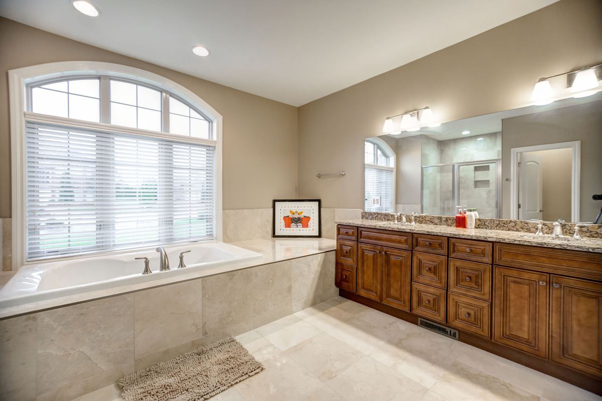 Bathroom with a built-in bathtub and double sink and long mirror.