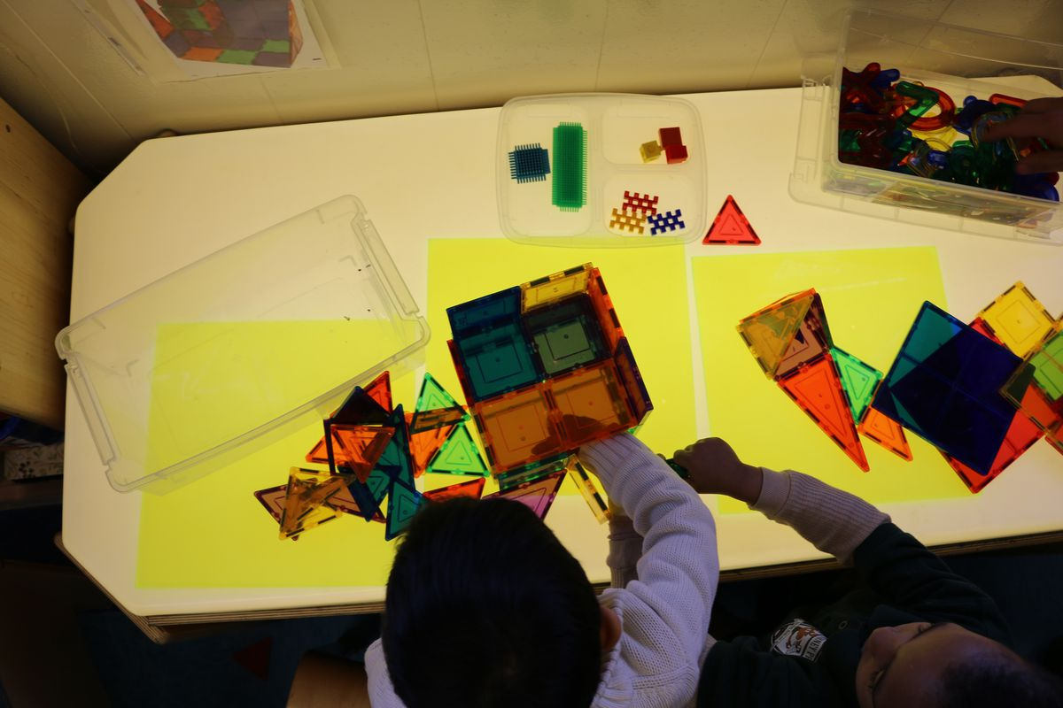 Pre-K students at P.S. 69 Journey Prep play with magnetic blocks on a light-up table.