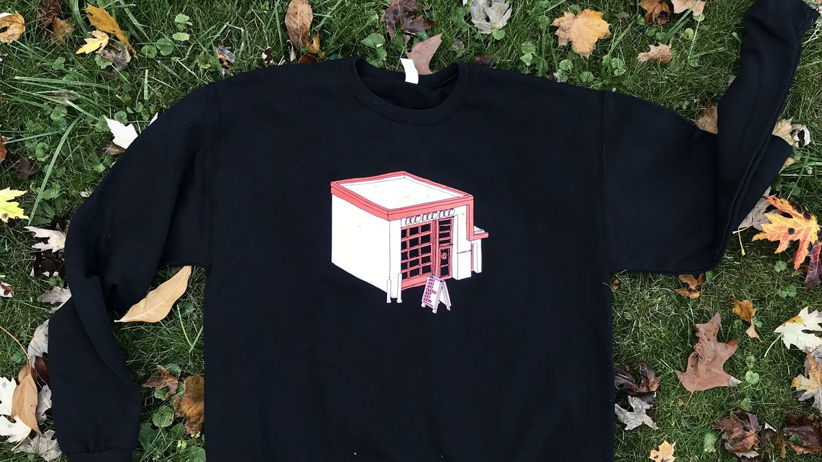 A black crew neck sweatshirt with a pink illustration of the Bon Bon Bon shop on the front is laid out on the grass surrounded by fall leaves.