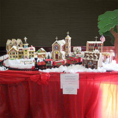 A gingerbread village with with 3 chapels and a house.