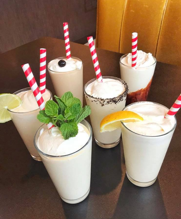 A group of decorated milkshakes with red and white straws.