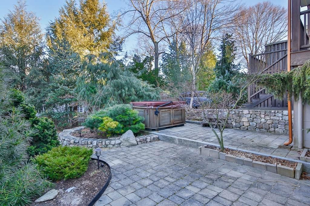A spacious stone patio with a hot tub in the background.
