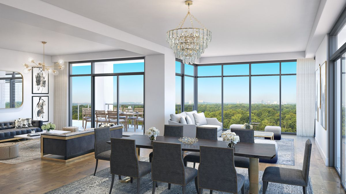 A huge condo dining room with views across trees to a city.