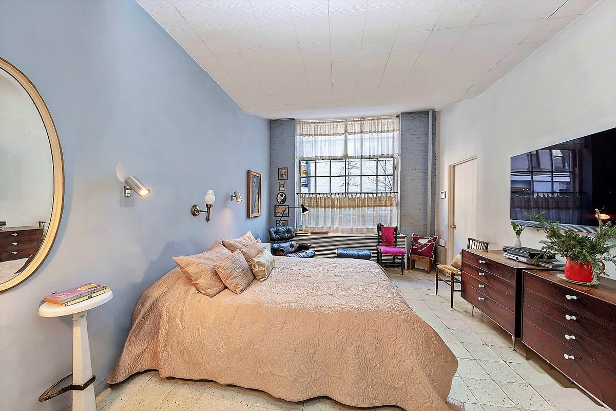 The one traditional bedroom at the front of the first floor apartment has a large window and blue walls.