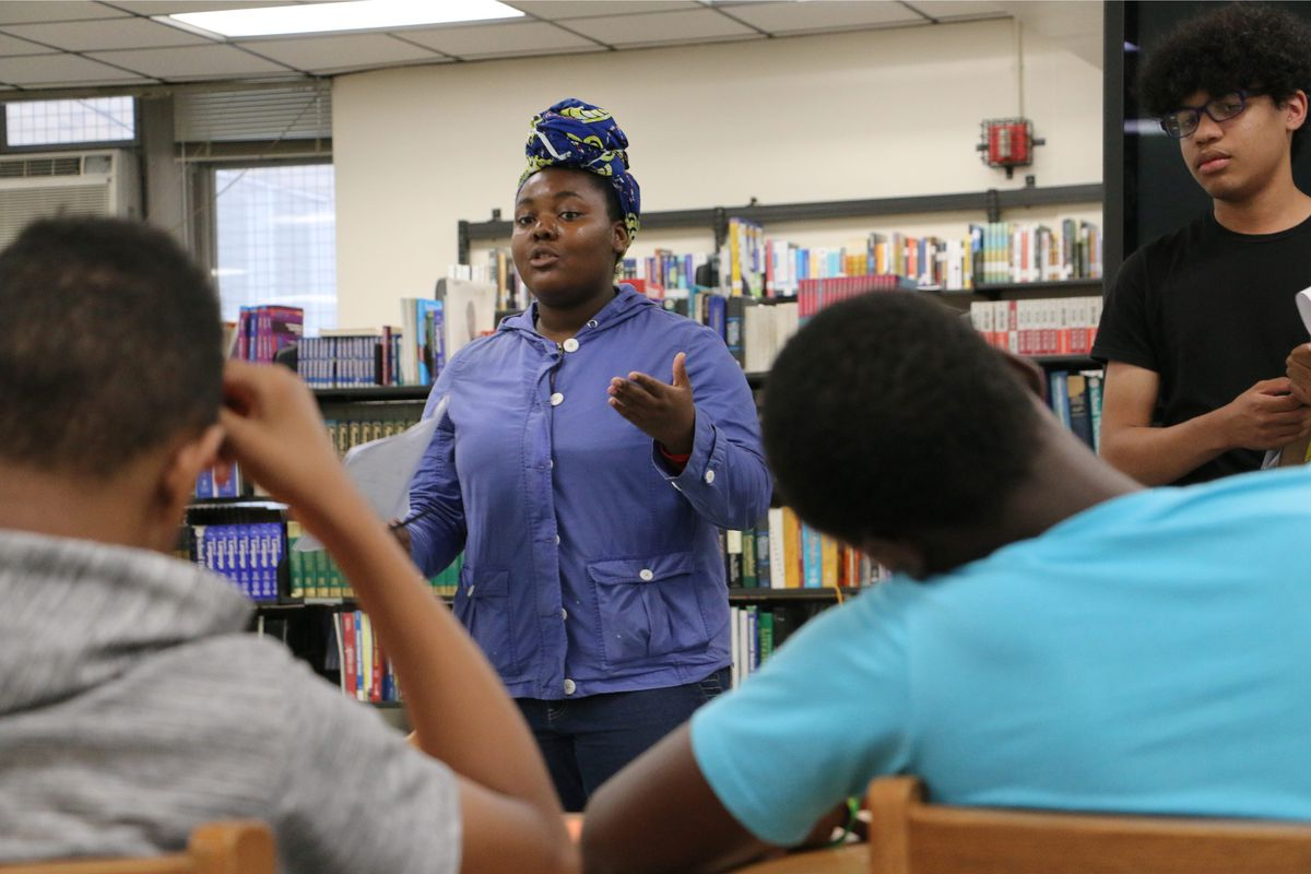 A Black girl in a blue shirt talks to a group of students in a high school. She's in front of a bookshelf.