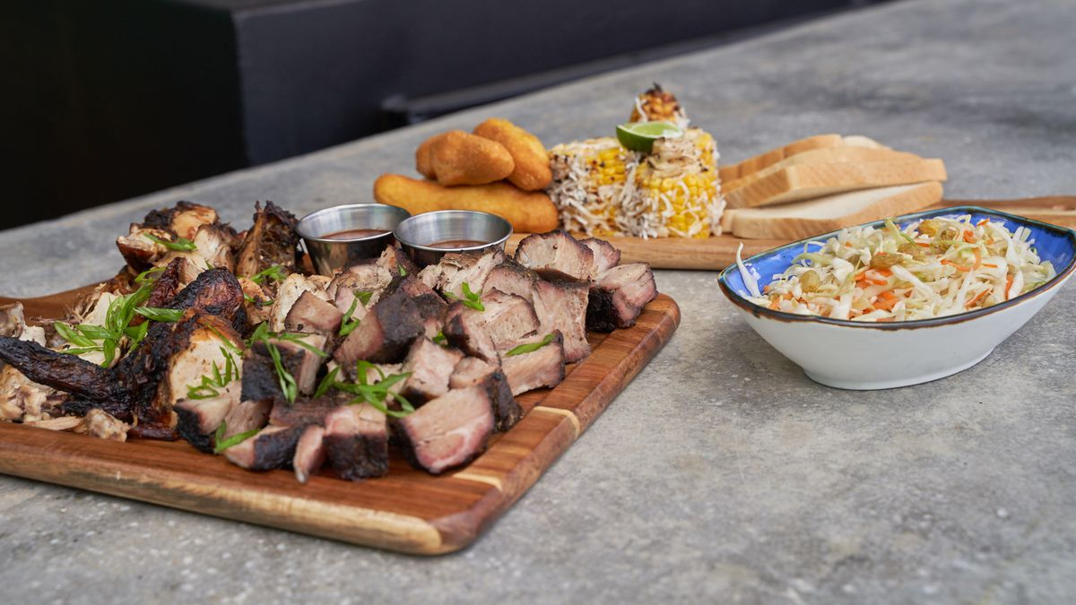 a variety of dishes with a large meat dish in the center on top of a wooden board
