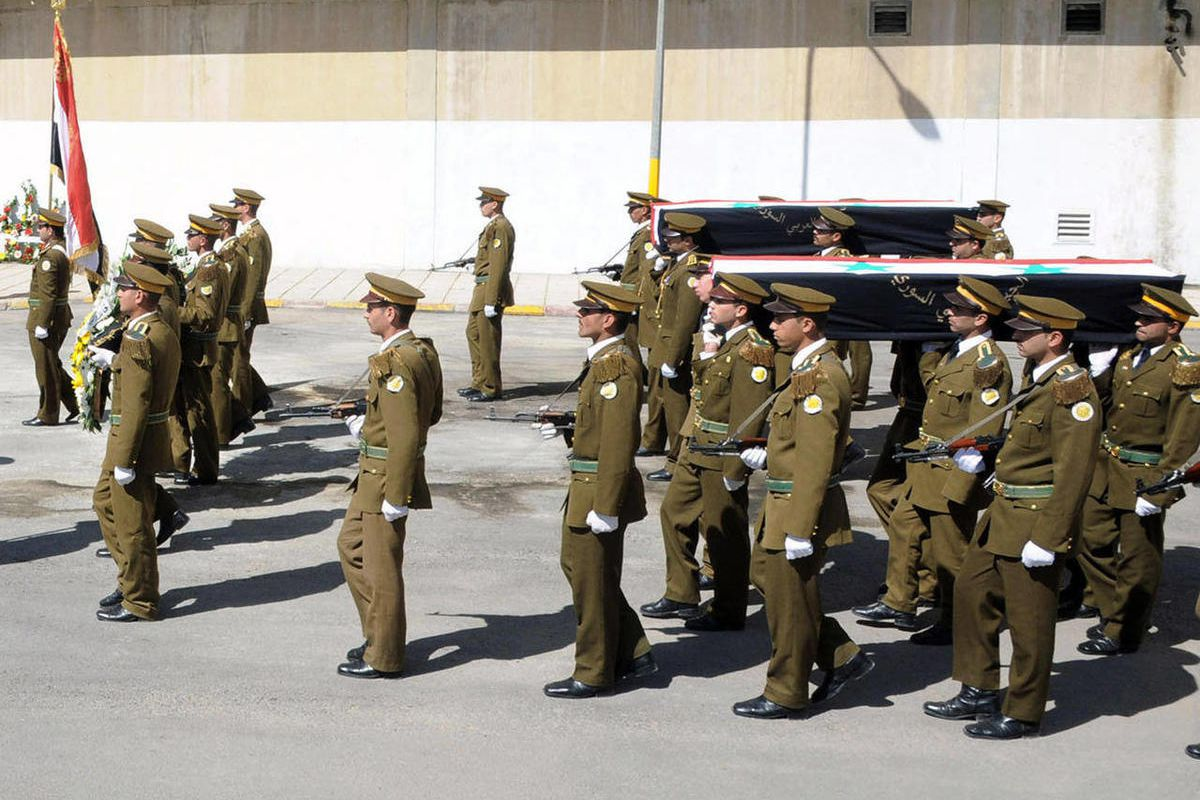 In this photo released by the Syrian official news agency SANA, Syrian honor guard soldiers carry the coffins of Syrian army soldiers who were killed in recent violence in the country, during their funeral procession at the military hospital in Damascus,
