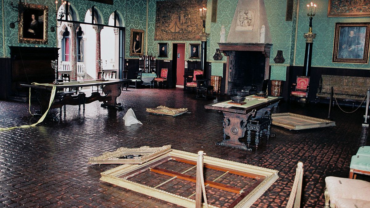 An archival photo of a room at the museum, with empty frames set on the floor in several places.