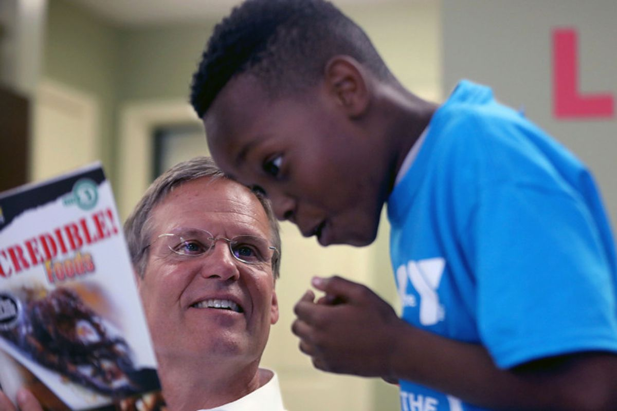 Tennessee Gov. Bill Lee reads to a child while visiting an apartment complex in Memphis on Tuesday.