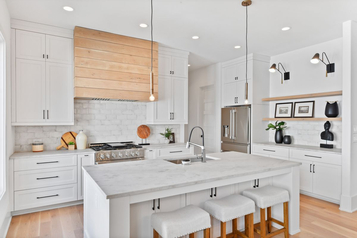 White kitchen with large island, plus barstools, stainless steel appliances, recessed lighting, and hardwood floors.