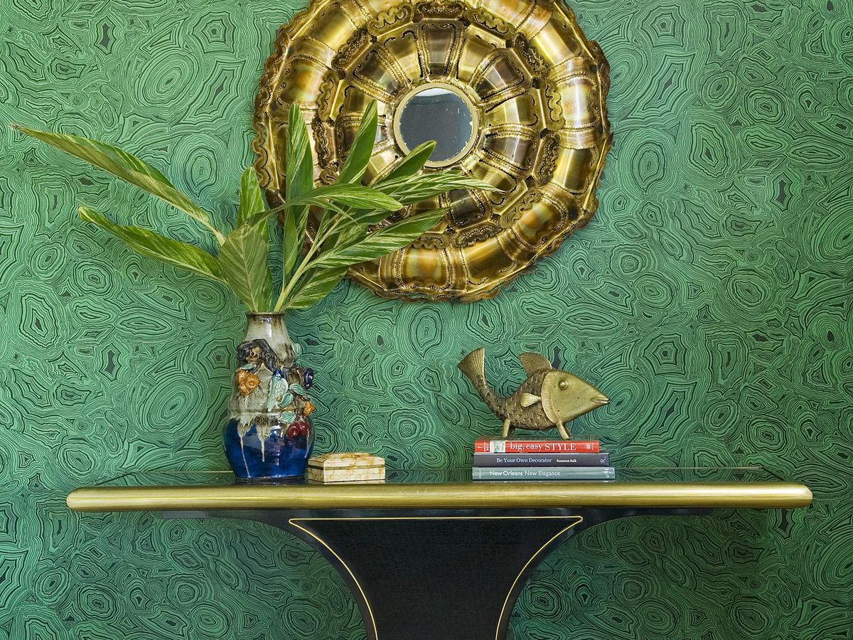 An interior in the Malachite Home in New Orleans. There is a shelf with a vase and a stack of books. The shelf is against a green wall. The wall has a gold mirror hanging on it.