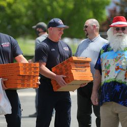 Wesley LeFevre and Patrick Cook, both firefighter-paramedics with the Layton Fire Department,hold boxes of Little Caesars pizza delivered by the organizers of the Sounds of Freedom Festival atFire Station No. 51 in Layton on Friday, May 15, 2020.Festival organizers dropped off pizzas at the Davis County Sheriff's Office, the Farmington Fire Department, and the Layton and Clearfield fire departments while driving in a restored 1939 firetruck that was used at Kennecott Copper in the '40s and restored for Shriner's Hospital for Children.