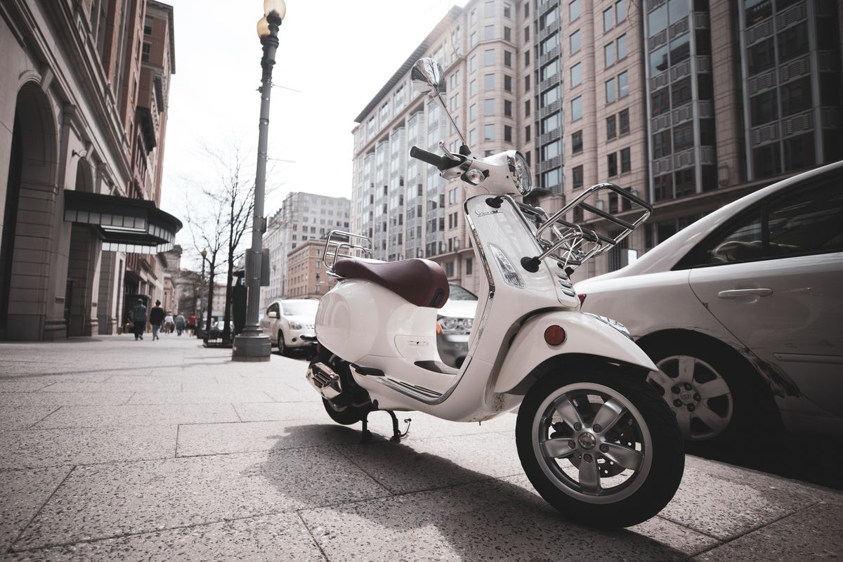 A white moped with a brown leather seat parked on a sidewalk in downtown D.C.