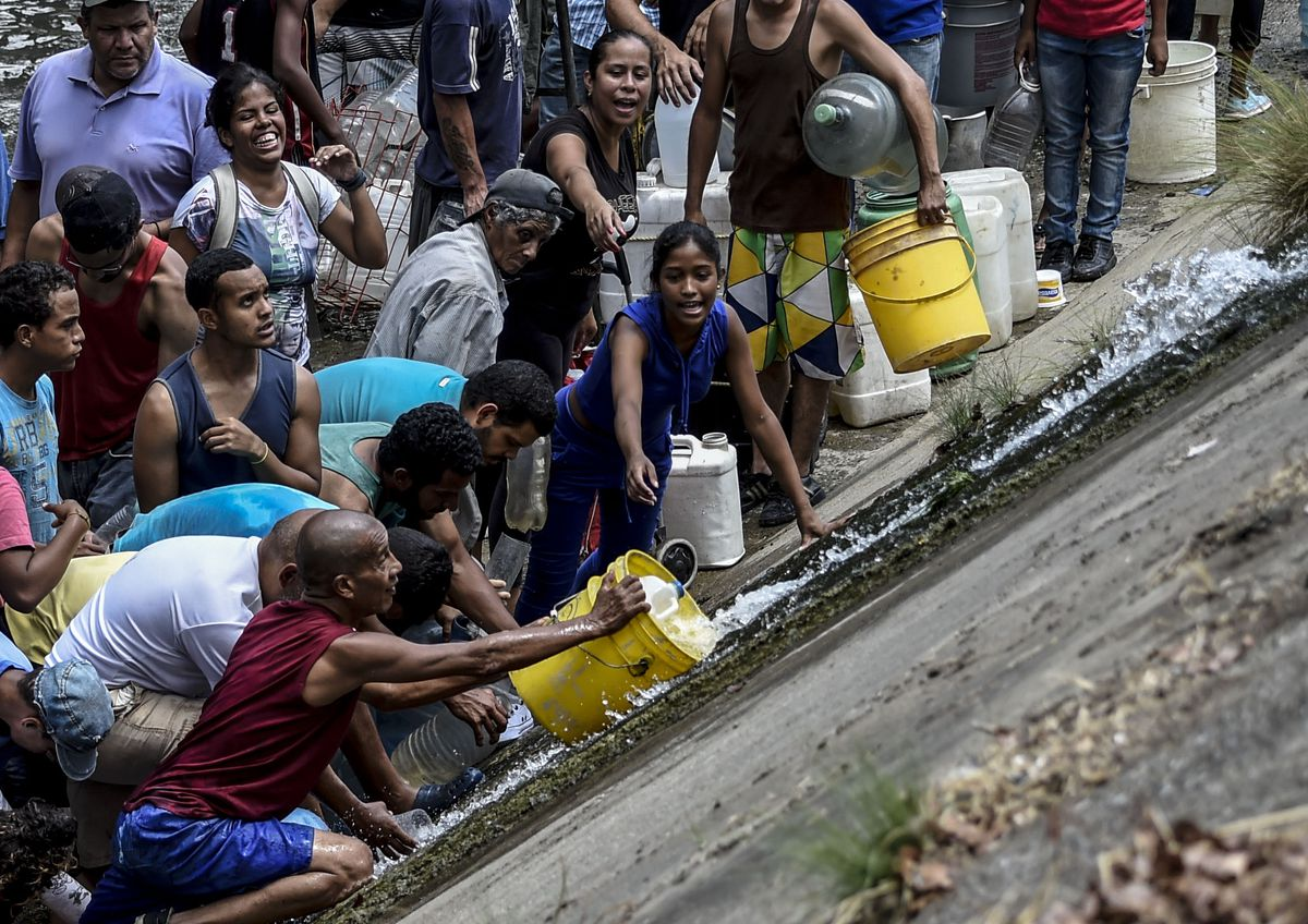 People collect water from a sewage canal at the river Guaire in Caracas on March 11, 2019, as a massive power outage continues affecting some areas of the country.