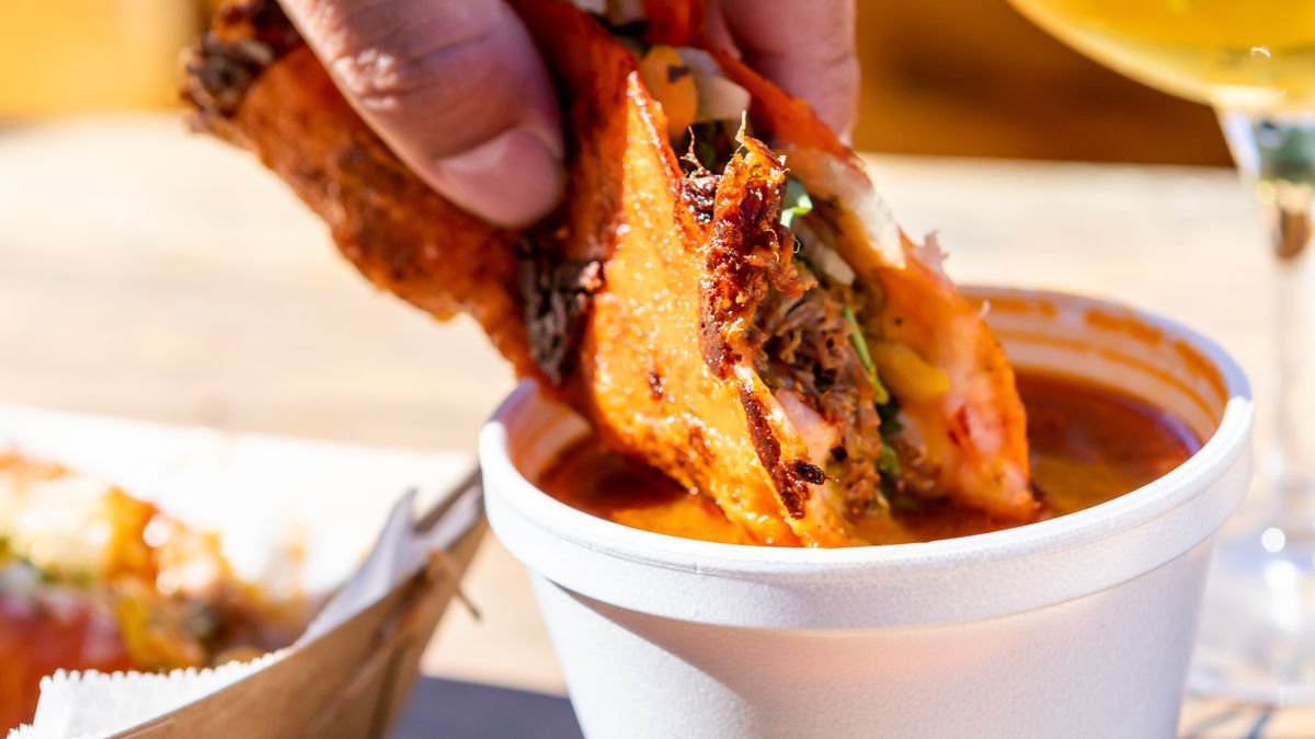 A hand dips a birria taco into comsomme