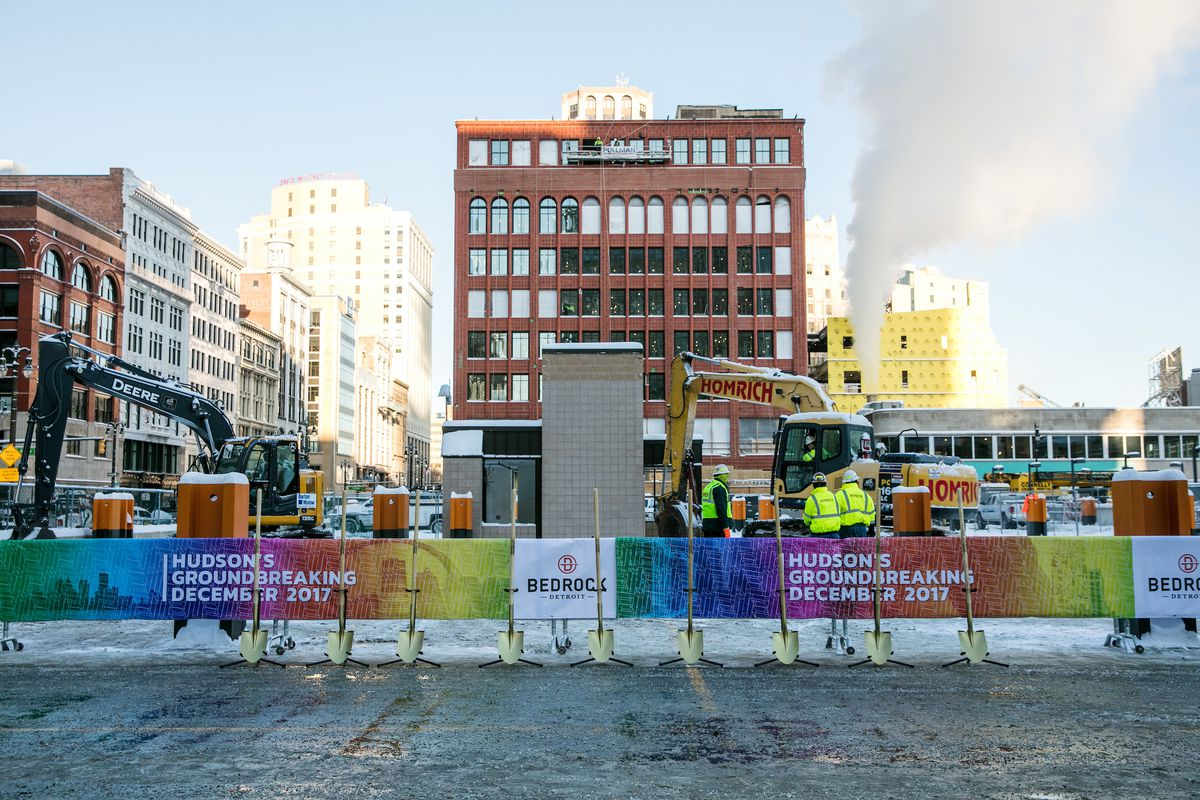"""A red brick building stands behind a site with construction equipment in winter. A rainbow colored flyer around a fence that says """"Hudson's Groundbreaking December 2017."""""""