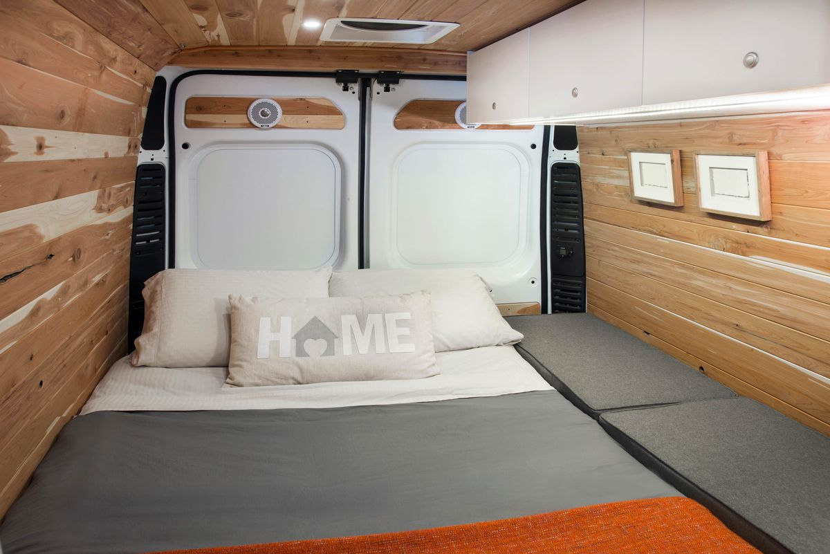 The interior of a camper van. The walls and ceiling are wood paneled. There is a bed with grey, white, and orange bed linens. There are multiple pillows on the bed including a pillow with the word: Home.