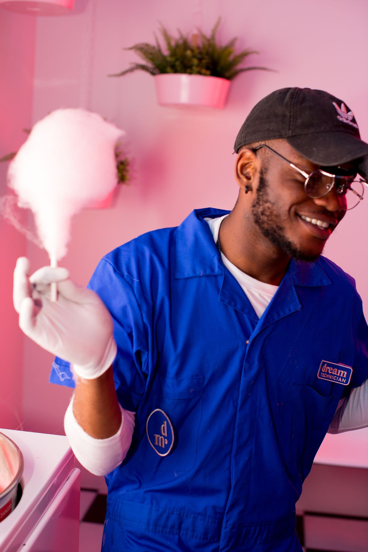 Dream Machine employee with cotton candy in left hand, pink background with plants
