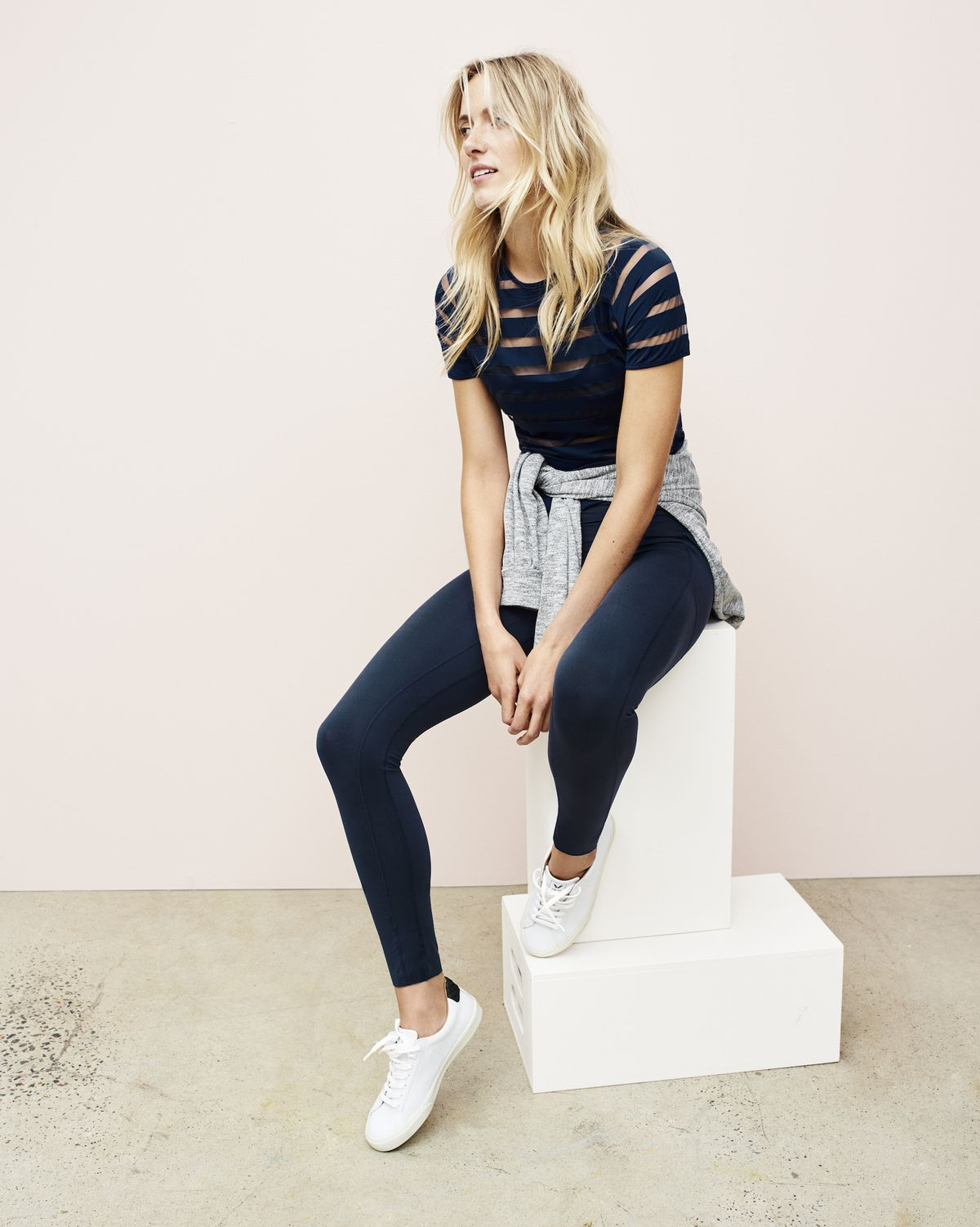 A model wearing navy blue leggings and a navy blue shirt