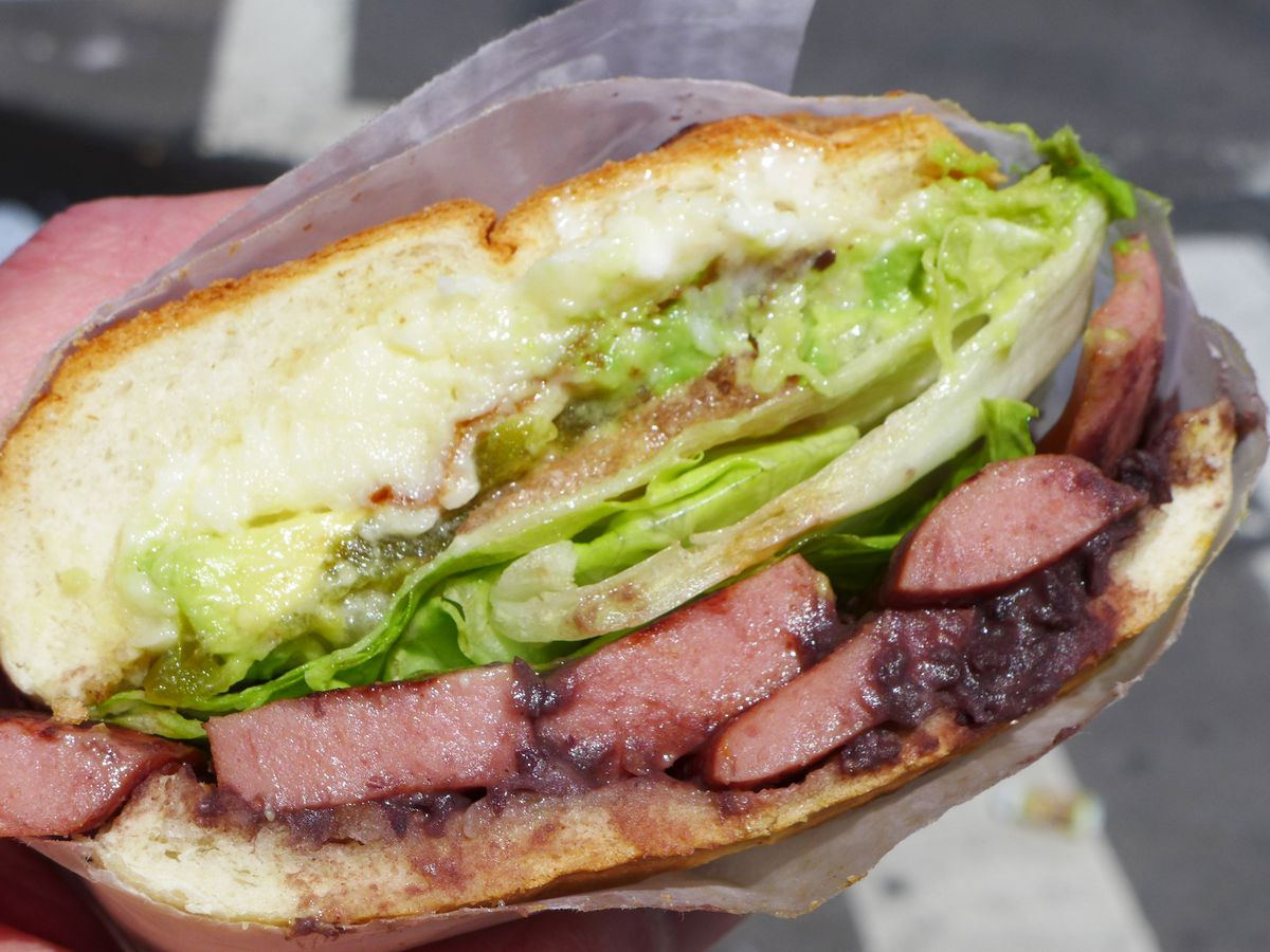 A round sandwich oozing guacamole with many hot dogs inside.