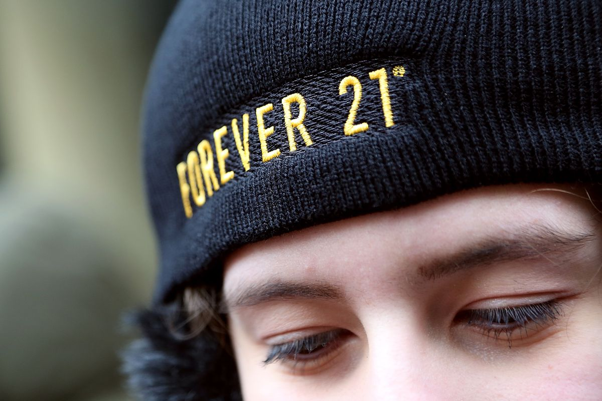 """A person wears a black hat with """"Forever 21"""" written across it."""